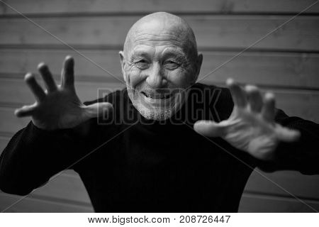 Black and white horizontal capture of handsome happy senior expressing positivity and young soul, playing with camera and laughing. Old senior man closeup portrait. People, feelings, human concept.