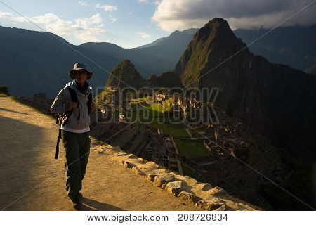 Tourist walking at Machu Picchu illuminated by the last sunlight. The Inca's city is the most visited travel destination in Peru.