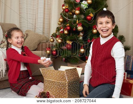 Child unpack gift boxes near christmas tree, show a handful of snow, decoration at home, happy emotion, winter holiday concept