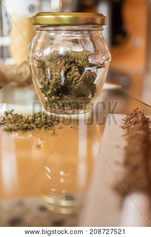 Medical Cannabis in jar and tobacco on a table
