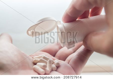 White Pills spill out of container on hand