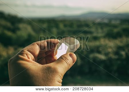 Prism in hand in front of a Landscape