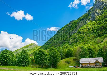 The House Of Wooden Logs Stands Alone In The Middle Of The Mountains.