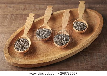 Spoons with chia seeds on wooden dish