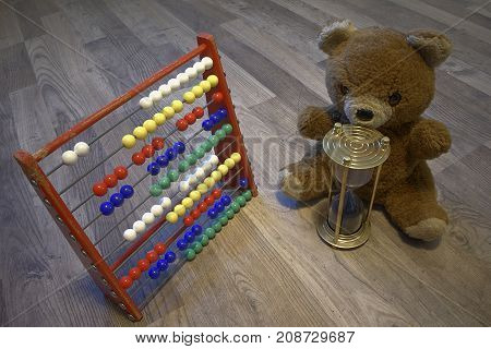 Teddy bear watching a brass timeglass that has ran out of sand /time. Childrens calculator.