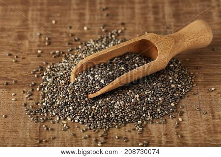 Scoop with chia seeds on wooden table