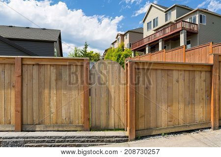 House backyard new wood fence garden gate door in suburban residential neighborhood