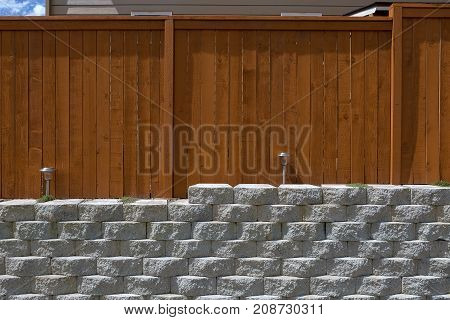 Wood fence cement stack stone blocks retaining wall and landscaping lighting front view