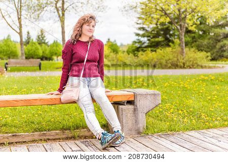 One Young Happy Woman Sitting On Bench On Boardwalk Sidewalk In Green Downtown City Park In Saguenay