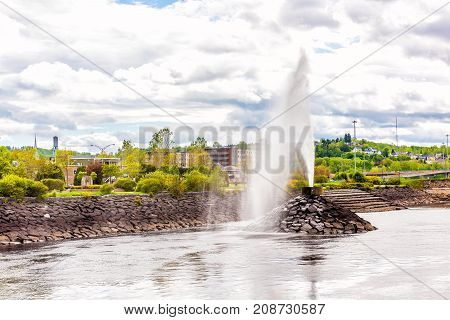 Water fountain stream shooting up in downtown city park in Saguenay Quebec Canada during summer