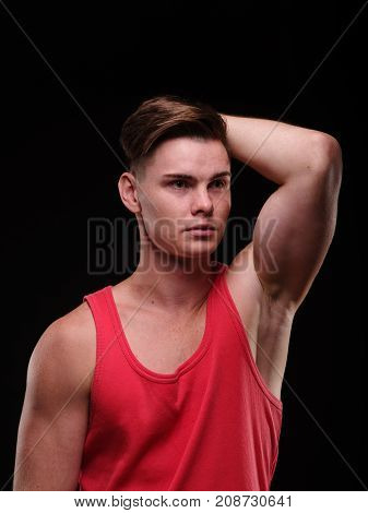 Portrait of a young man on a black background in a red tank top. Looking away. Close-up.