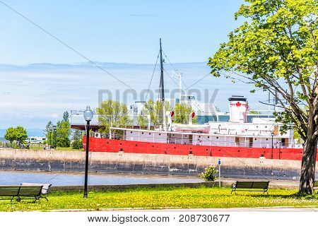 L'Islet Canada - June 4 2017: Saint Lawrence river beach shore with view of red ship and Canadian maple leaf in Musee maritime du Quebec Capitaine J.E. Bernier