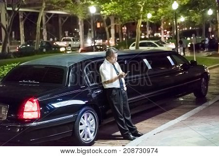 Washington Dc, Usa - August 4, 2017: Limo Limousine Driver Standing By Car Sidewalk Looking At Mobil