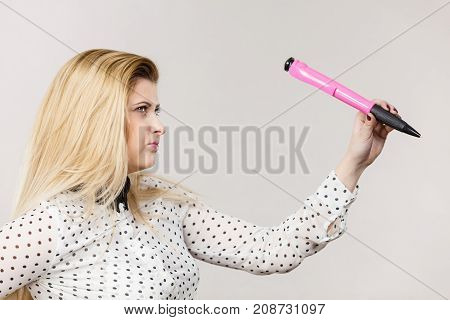 Woman holding big oversized pen. Studio shot on light background with copyspace.