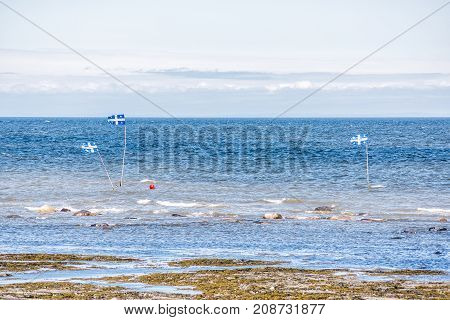 Blue Quebec, Canada Flags On Saint Lawrence River Or Gulf Buoys On Beach Shore With Nobody During Da
