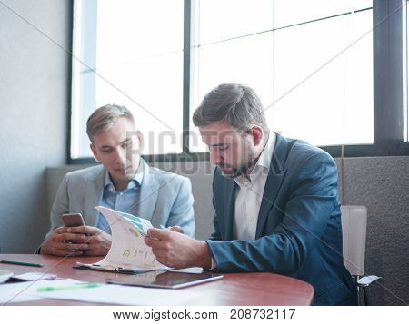 Two businessmen in expensive suits consider the papers work in a team to quickly solve problems