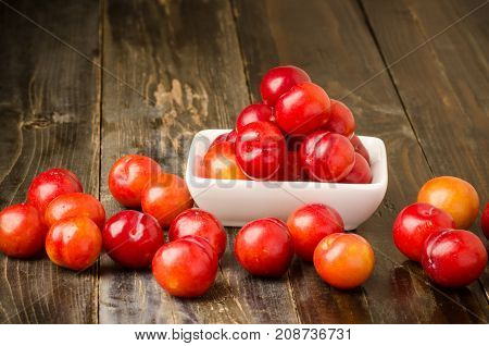 Fresh plum fruit (Julee) in a small bowl on wooden background, healthy fruit