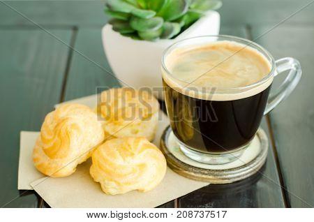Breakfast, vanilla choux and cup of hot espresso coffee