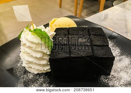 The black toast bread with whipped cream and vanilla ice cream serve on black dish for dessert background.
