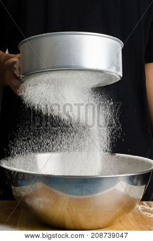 Homemade bakery cooking, sifting flour into a bowl