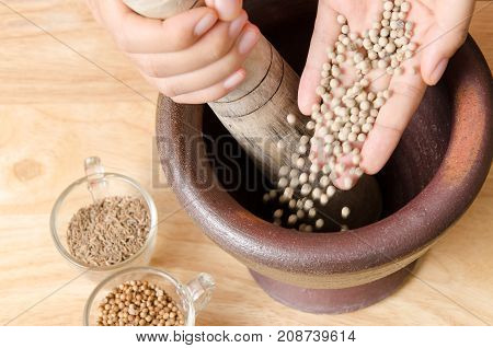 Thai food cooking,Hand pouring white pepper seed in a mortar and pounding for making curry