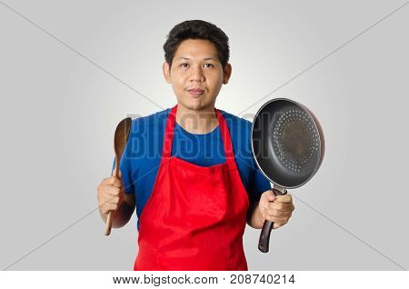 Asian man wear red apron and holding ladle and pan for cooking isolated on gray background