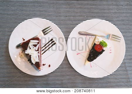 Piece of cake on white dish, Red velvet cake and blueberry cheesecake, top view of food