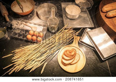 Cluttered kitchen by a beginner of homemade bakery with baking ingredients as flour rolling pin whisk egg shells mesh and plastic molds for baking. Pile the flour into a bowl with the egg yolk top view
