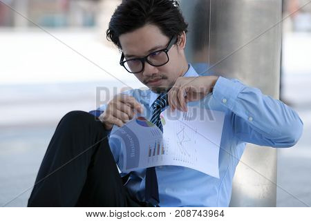 Frustrated stressed young Asian business man tearing up charts at outside office