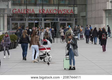 Galeria Krakowska shopping centre main square with entry Cracow Poland - October 13 2017: People are walking in and out through Galeria Krakowska main square with entry the tourist women is looking for information in her mobile phone Cracow Poland.
