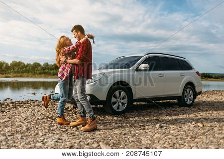 Young Couple Dressed Alike In White T-shirt And Checkered Shirt Hugging Near The Car And Rivers