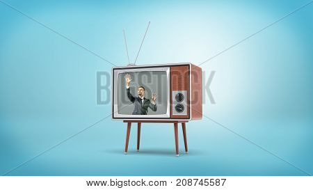 A businessman inside a retro TV screen puts his hands flat on the screen from the inside. Business technologies. Caught in hi-tech. Distance communication.