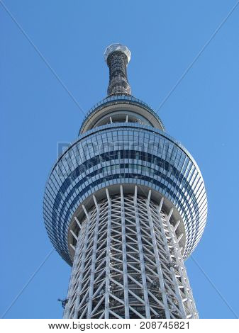 Sumida Tokyo Japan, 20 December 2012: Closeup View of the top of Tokyo Skytree Neofuturistic television and radio broadcast supertall tower with clear blue sky