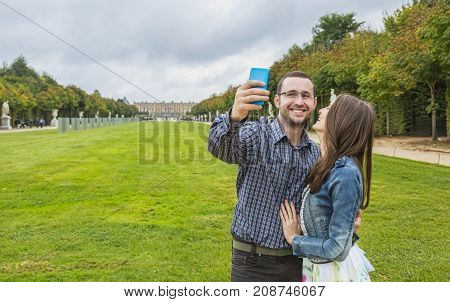 Lovely young couple taking a selfie outdoors in a garden.