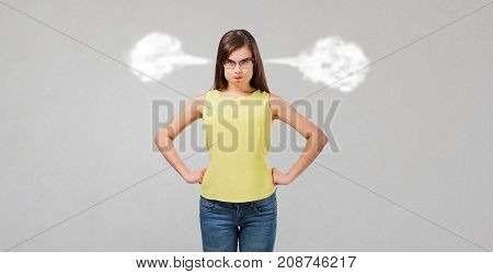 Dissatisfied wicked girl on a gray background. The woman lets out steam from ears. Human emotions.
