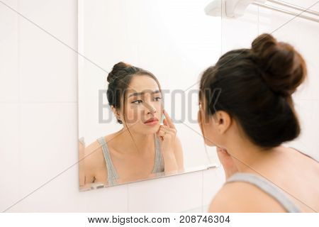 Smiling young woman looking to mirror at home bathroom