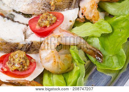 Stuffed seabass with shrimp and vegetables on plate