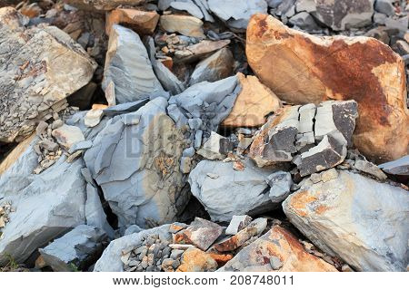 Cracks and colorful layers of sandstone background. A big heap of sandstones storage space of various natural sandstone. The pattern of the variegated sandstones. Layers of toning colored big stones