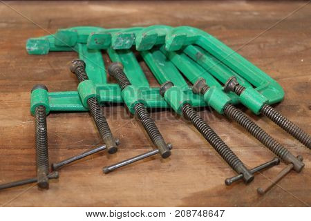 Group of c clamp tools on table wood background.