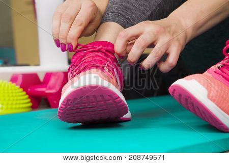 Sport Girl Tying Her Shoes,female Runner Tying Her Shoes Preparing For A Run,fitness Exercise In Gym