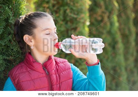 Beautiful girl drinking water after jogging in outdoor. A  beautiful girl is drinking water the hot sun in the park. Healthily concept. Healthy lifestyle concept. copy space. Portrait  beautiful girl
