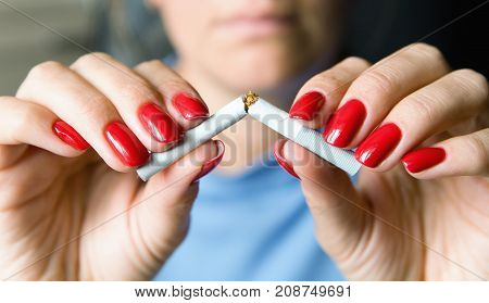 Fighting nicotine addiction. A girl with a beautiful manicure breaks a cigarette.