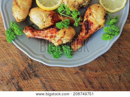Grilled chicken legs with mustard on cutting board.Rustic dinner background . Top view .