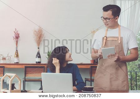 Young Asian man wear apron talking and receive order from customer at working table in coffee shop with smile face.Concept of cafe and coffee shop small business.