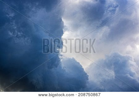 The sky is dark, swirling clouds. The clouds are dark blue, and the sun shines through them. Clouds are predicting rain.