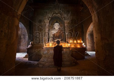 Bagan Myanmar - December 21 2016: Young novice monk praying with candles in front of buddha statue inside old pagoda Bagan Myanmar