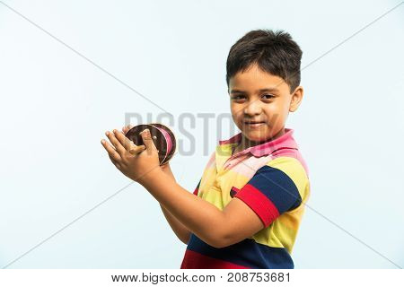 Kite or Patang flying in India, cute and happy little indian boy/kid holding chakri or wooden spindal and standing over blue background on Makar Sankranti Festival