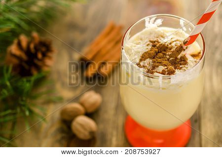 Christmas homemade sweet drink: eggnog with cinnamon nutmeg and whipped cream in glass on wooden rustic background. Traditional Christmas dessert. Selective focus.