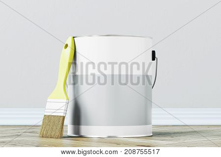 Close up of a gray paint bucket standing on a wooden floor against a white wall with a large paintbrush near it. 3d rendering mock up