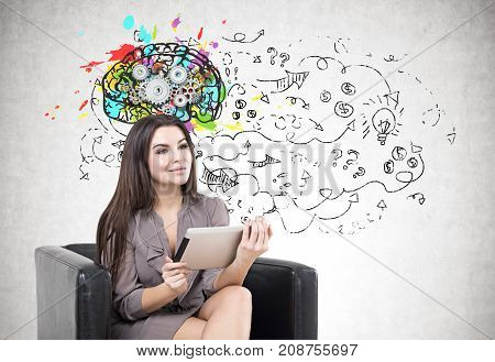 Portrait of a young smiling businesswoman wearing a suit and holding a digital tablet while sitting in an armchair. Gray background a cog brain sketch and arrows